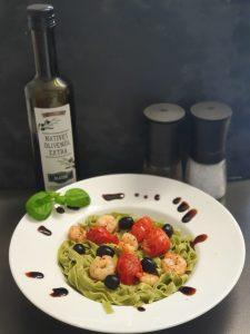 Grüne Spirulina-Bandnudeln selbst gemacht mit Garnelen, Tomaten und schwarzen Oliven