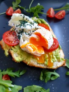 Brötchen mit Avocado, Tomate, poschiertem Ei und Spirulina-Granulat