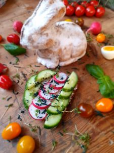 Frohe Ostern - Stulle mit Frischkäse, Gurke, Radieschen, Kresse und feinem Spirulina Granulat (im Hintergrund ein gebackener Osterhase)