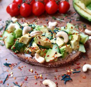 Deftiges Brot mit Avocado, Cashewkernen, Chili und feinem Spirulina Granulat - Serviert auf einem rustikalen Holzbrett