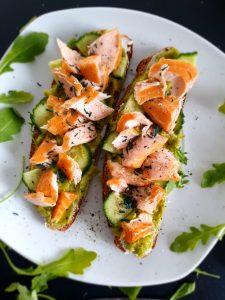 Reichlich belegtes Brot mit Avocado, Salatgurke, Stremel-Lachs und feinem Spirulina Granulat