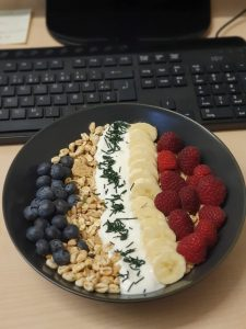 Müsli-Bowl mit Himbeeren, Bananen, Heidelbeeren und feinem Spirulina-Granulat (am Arbeitsplatz)