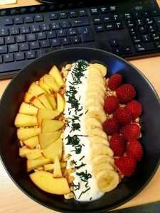 Müsli-Bowl mit Himbeeren, Bananen, Apfel und feinem Spirulina-Granulat (am Arbeitsplatz)
