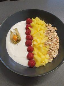 Müsli-Bowl mit Himbeeren, Mango, Physalis und feinem Spirulina-Granulat