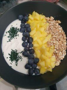 Müsli-Bowl mit Heidelbeeren, Mango und feinem Spirulina-Granulat
