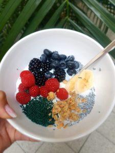 Müsli-Bowl mit Himbeeren, Brombeeren, Heidelbeeren, Bananen und feinem Spirulina-Granulat