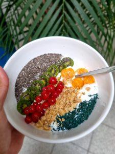 Müsli-Bowl mit Joghurt, Milch, Johannesbeeren, Mini-Kiwi, Physalis, Quinoa und feinem Spirulina-Granulat