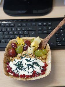 Müsli-Bowl mit hellen und dunklen Trauben, Apfel, Granatapfel, Pfirsich und Spirulina-Granulat (am Arbeitsplatz)