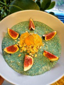 Grüne Porridge-Bowl mit Stücken von Feige